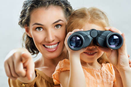 little girl looking through binoculars photo