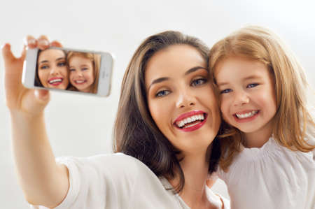 mother with daughter: madre e hija haciendo una selfie Foto de archivo