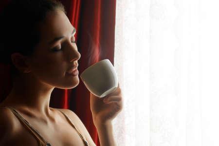 mujer tomando cafe: Mujer con un aromático café en mano Foto de archivo