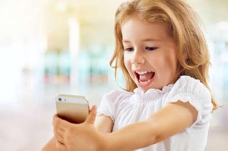 pretty little girl: a beauty child taking selfie