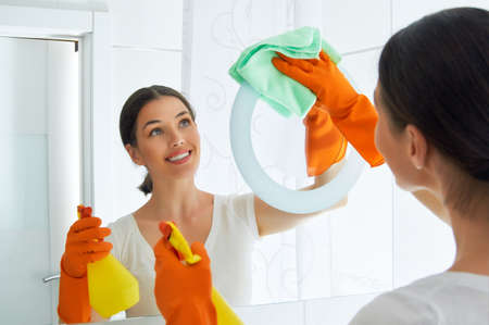 bright housekeeping: beautiful girl cleans the surface
