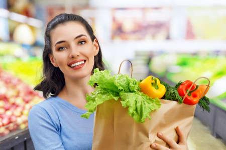 a woman holding a bag of fruit Фото со стока