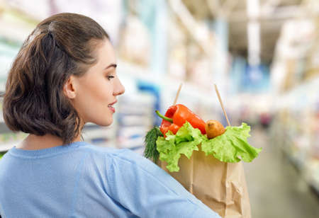 food stores: a woman holding a bag of fruit Stock Photo