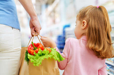 grocery shopping: mother and daughter holding fruit