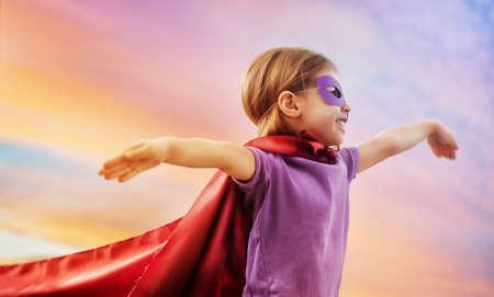 a little girl plays superhero photo