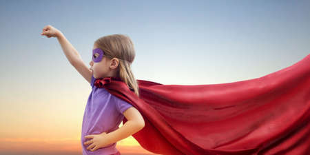 costumes: a little girl plays superhero Stock Photo
