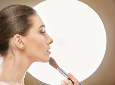 mujer maquillandose: muchacha hermosa que sostiene un cepillo Foto de archivo