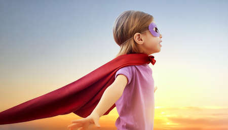 kid  playing: a little girl plays superhero Stock Photo