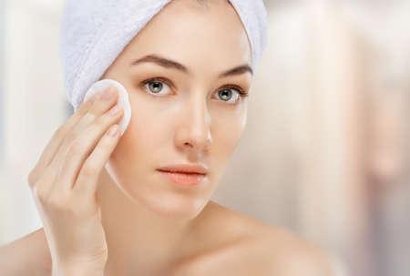 volti: bella donna applicando la crema cosmetica