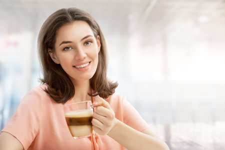 latte macchiato: Woman with an aromatic coffee in hands