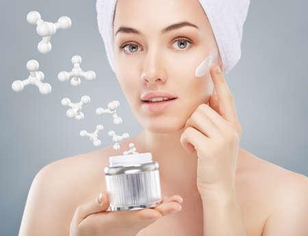 美しい女性の化粧品のクリームを適用します。 写真素材