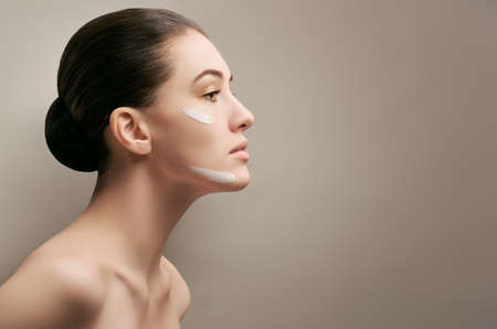 woman face cream: beauty woman on the grey background Stock Photo