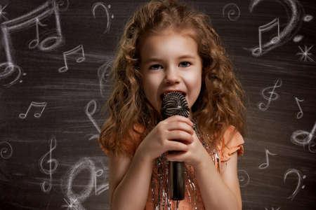 niño cantando: Niño de la belleza en la pizarra Foto de archivo