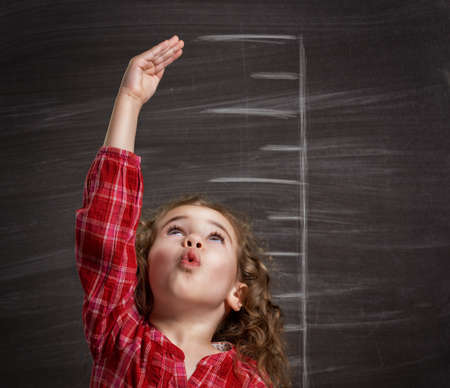 tall and short: beauty child at the blackboard Stock Photo