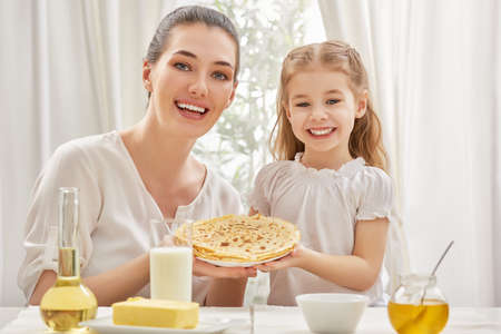 mother and daughter prepare pancakes