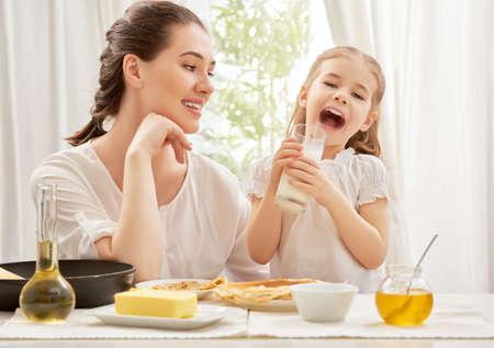 ni�os desayuno: ni�a bebiendo leche en la cocina