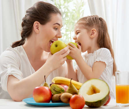 people eating: familia feliz comiendo fruta fresca