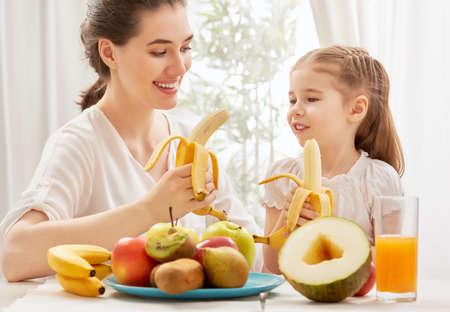 comiendo platano: familia feliz comiendo fruta fresca