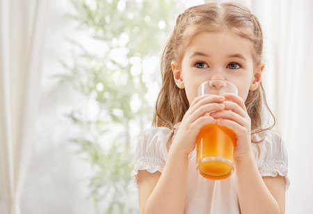jugos: Una ni�a hermosa que bebe el jugo fresco