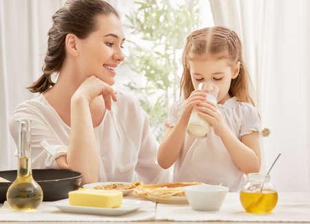 madre e hijos: niña bebiendo leche en la cocina