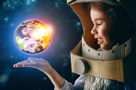 mundo manos: niño está vestido con un traje de astronauta Foto de archivo