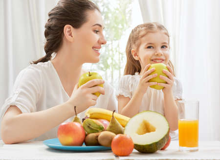 fruit juices: happy family eating fresh fruit Stock Photo