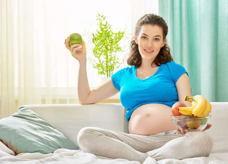 happy pregnant woman eating fruit Stock Photo