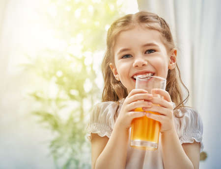 tomando jugo: Una niña hermosa que bebe el jugo fresco