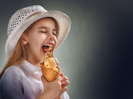 little girl eating ice cream Фото со стока