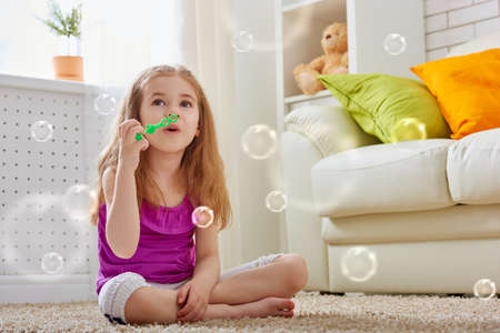 blowing: little girl blowing soap bubbles Stock Photo
