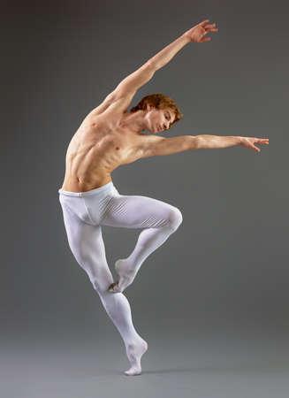 leap: modern ballet dancer on grey background