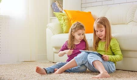 niños sentados: niños felices celebración de la tableta digital Foto de archivo