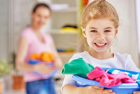 trabajando en casa: familia con una palangana llena de ropa