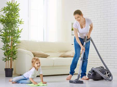 orden y limpieza: familia feliz limpia la habitación Foto de archivo