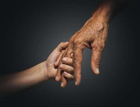 cogidos de la mano: jóvenes y adultos de palma Foto de archivo