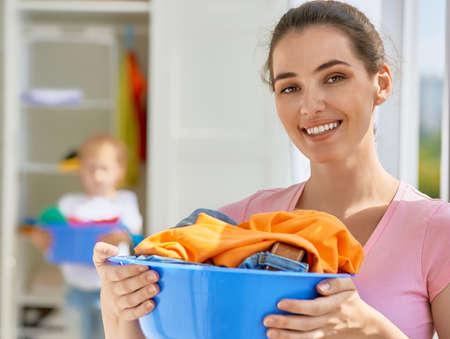 lavando ropa: familia con una palangana llena de ropa