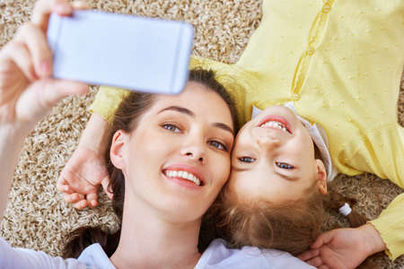 daughter mother: mother and daughter making a selfie Stock Photo