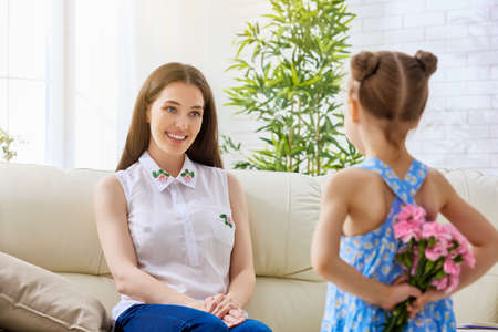 cute little girl: mother and daughter with flowers Stock Photo