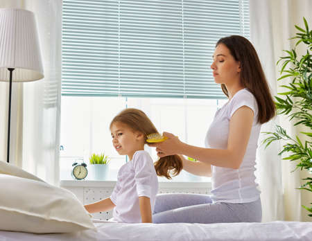combing: mother combing her daughters hair