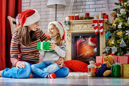 familias jovenes: Madre e hija intercambio de regalos de Navidad