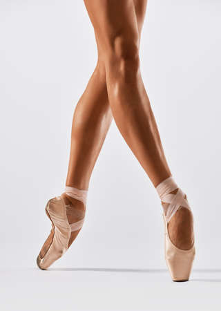 Ballerina dancing on point in studio Stock Photo