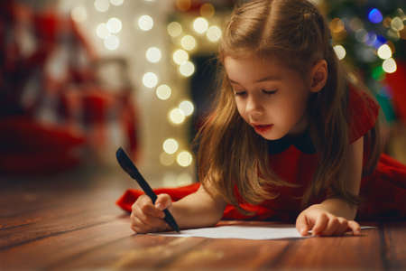 xmas: small child writes the letter to Santa Stock Photo