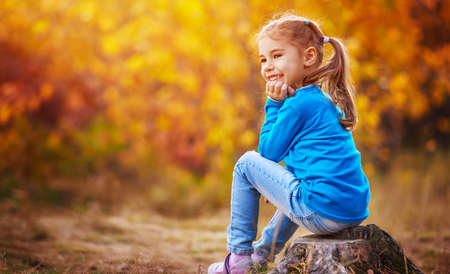 happy little child, baby girl laughing and playing in the autumn on the nature walk outdoors