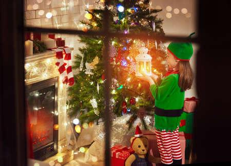 Meisje in kostuum van Kerstmiself die zich met een lantaarn in haar hand door de Kerstboom bevinden