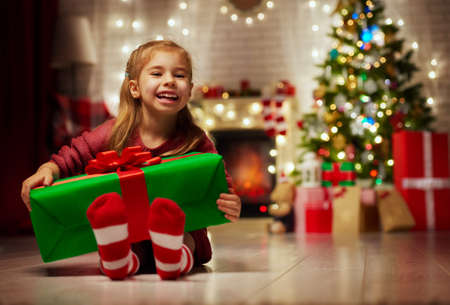 Funny smiling child holding Christmas gift in hand.