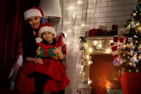 young child: mother and daughter by fireplace on Christmas Stock Photo