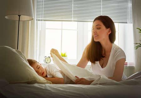 enfant qui dort: Portrait de jeune mère couvrant petite fille de dormir avec une couverture Banque d'images