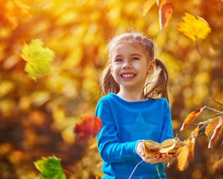 cute little girl: happy little child, baby girl laughing and playing in the autumn on the nature walk outdoors