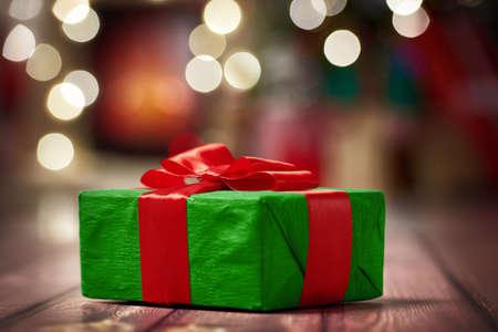 Vánoční dárky s červenou stuhou na tmavém dřevěném pozadí