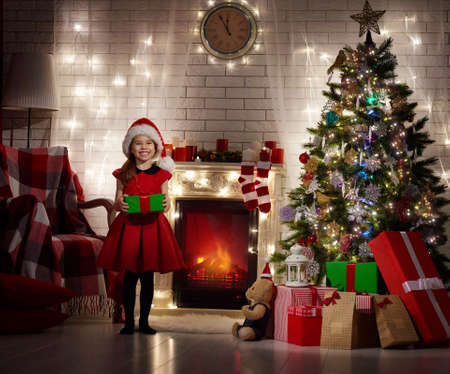 miracle tree: Funny smiling child holding Christmas gift in hand.